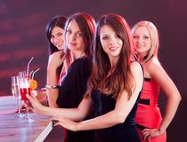 Beautiful women on a night out. Four beautiful fashionable women on a night out standing at a bar counter with their drinks Royalty Free Stock Photography