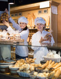 Beautiful women offering bread and different pastry Stock Images