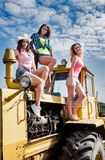 Beautiful women on old big tractor Stock Images