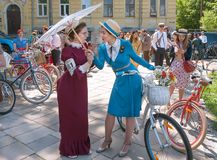 Beautiful women in old fashion dresses talking about vintage bicycle during outdoor festival Retro Cruise royalty free stock photos