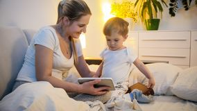 Beautiful young woman in pajamas with her 2 years old son watching cartoons on digital tablet at night. Beautiful women in pajamas with her 2 years old son royalty free stock photos