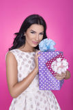 Beautiful women in pink background with present. Party. Love. Gift. Royalty Free Stock Images