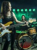 Beautiful women playing in the rock band. Photo of a female bass player and drummer of a rock band playing on stage Royalty Free Stock Photography