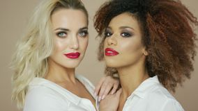 Beautiful women posing and looking at camera. Portrait of two sensual pretty women friends with red lips looking at camera and posing in studio together stock video
