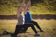 Beautiful women praising yoga during obstacle course Stock Images
