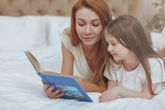 Charming woman reading a book to her little daughter stock image