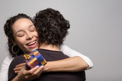 Young woman receives Christmas present. Happy girlfriend hugs he royalty free stock photography