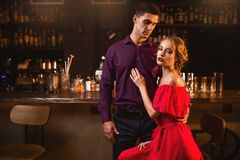 Woman in dress with her man against bar counter. Beautiful women in red dress with her men against bar counter. Date in nightclub, attractive love couple in pub Stock Photography