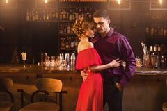 Woman in red dress hugs with her man in bar. Beautiful women in red dress hugs with her men in bar. Date in nightclub, attractive love couple in pub Royalty Free Stock Photo