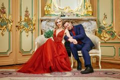 A beautiful woman in a red dress with a man sitting in a chair, the bride and groom, happy newlyweds stock photo