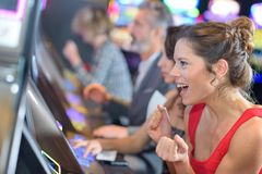 Beautiful woman in red dress playing slot machine. Beautiful women in red dress playing slot machine slot royalty free stock photo