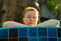 Beautiful women with red hair is enjoying the pool Stock Photos
