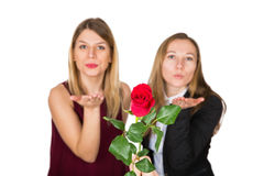 Beautiful women with red rose sending a kiss. Picture of two beautiful women sending a kiss and holding a red rose on an isolated background Royalty Free Stock Photos