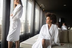 Beautiful black woman relaxing at luxury hotel spa wearing bathrobe looking at window portrait. Beautiful women relaxing at luxury hotel spa wearing bathrobe stock images