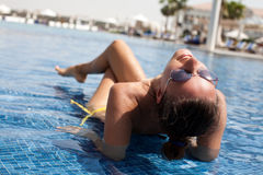 Beautiful women relaxing at the luxury poolside. Beautiful woman relaxing at the luxury poolside. Girl at travel spa resort pool. Summer vacation Royalty Free Stock Photography