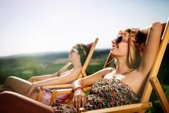 Women relaxing and sunbathing in summer. Beautiful women relaxing and sunbathing in summer royalty free stock image