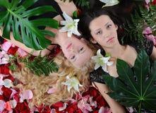 Beautiful women in rose petals Royalty Free Stock Images