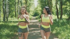 Beautiful women running in park. Blonde and brunette girls running outdoors stock video