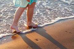 Beautiful women`s bare feet by the sea on the waves relaxation concept royalty free stock photos