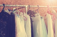 Beautiful women`s clothes hang on the hanger in the closet. Toning in the style of instagram. Close-up, soft focus royalty free stock images