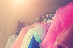 Beautiful women`s dresses hang on the hanger in the closet. Toning in the style of instagram. Close-up royalty free stock photos