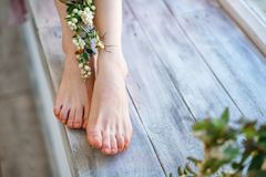 Beautiful women`s feet with flowers on wooden background, foot skin care stock photos