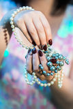 Beautiful women's hands holding pearl. Beautiful hand of a young woman with brown manicure holding white pearl necklace royalty free stock image