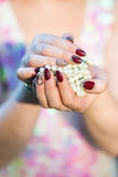 Beautiful women's hands holding pearl. Beautiful hand of a young woman with brown manicure holding white pearl necklace Royalty Free Stock Photos