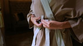Beautiful women`s hands tie the belt on the robe. Comfort and intimity.  stock video