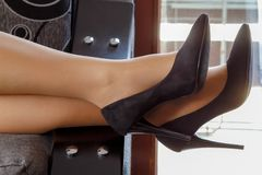 Beautiful women`s legs with black shoes on the bed royalty free stock image
