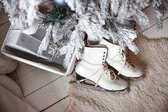 Beautiful women`s skates for figure skating white. Beautiful women`s skates for figure skating white lie next to the Christmas tree in a pile of gifts stock photos