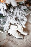 Beautiful women`s skates for figure skating white. Beautiful women`s skates for figure skating white lie next to the Christmas tree in a pile of gifts stock photo
