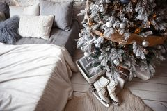 Beautiful women`s skates for figure skating white. Beautiful women`s skates for figure skating white lie next to the Christmas tree in a pile of gifts royalty free stock image
