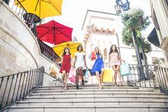 Beautiful women shopping. Multiethnic group of girls shopping - Four beautiful women having fun while buying some presents in a mall Stock Image