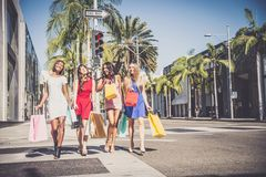 Beautiful women shopping. Multiethnic group of girls shopping - Four beautiful women having fun while buying some presents in a mall in Beverly Hills Royalty Free Stock Images