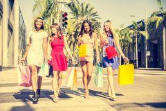Beautiful women shopping. Multiethnic group of girls shopping - Four beautiful women having fun while buying some presents in a mall in Beverly Hills Royalty Free Stock Photos