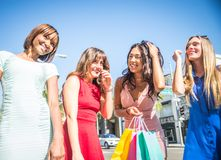 Beautiful women shopping. Multiethnic group of girls shopping - Four beautiful women having fun while buying some presents in a mall in Beverly Hills Stock Photography