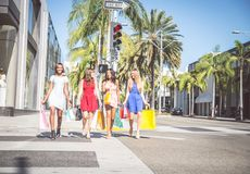 Beautiful women shopping. Multiethnic group of girls shopping - Four beautiful women having fun while buying some presents in a mall in Beverly Hills Stock Photo