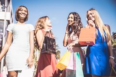 Beautiful women shopping. Multiethnic group of girls shopping - Four beautiful women having fun while buying some presents in a mall in Beverly Hills Stock Photos