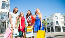 Beautiful women shopping. Multiethnic group of girls shopping - Four beautiful women having fun while buying some presents in a mall in Beverly Hills Stock Images