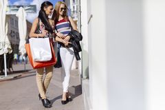 Beautiful women shopping spree. On street royalty free stock photo
