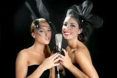 Beautiful women singing on a vintage microphone Royalty Free Stock Photo