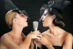 Beautiful women singing on a vintage microphone stock image
