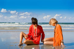 beautiful women sitting on beach Stock Image