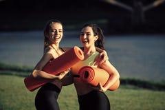 Beautiful women smile with yoga mats. Outdoor Stock Photos