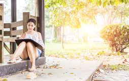 The beautiful women smilling and writing paper on the ground in the park stock photo