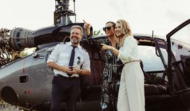 Beautiful women standing by helicopter with pilot royalty free stock photography