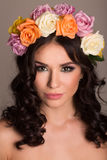 Beautiful women supermodel in wreath of flowers close up portrait. Series of photos made in studio. Royalty Free Stock Image
