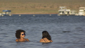 Beautiful women swimming in lake with house boats Royalty Free Stock Images