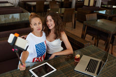 Beautiful women taking photo on mobile phone via self stick while sitting with touch pad and laptop computer in cafe, Royalty Free Stock Photography